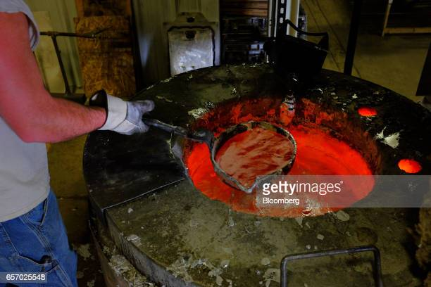 An employee scoops melted aluminum to pour into a mold while working in the foundry at the Super Vac Manufacturing Co production facility in Fort...