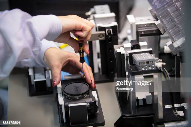 An employee screws the casing of a Leica CL digital camera on the assembly line at the Leica Camera AG factory in Wetzlar Germany on Tuesday Nov 28...