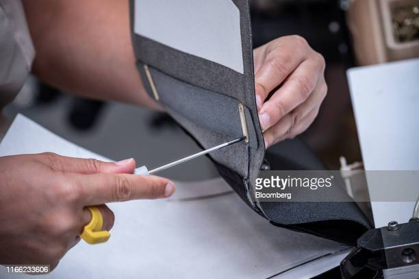 An employee secures a clasp fitting inside a luxury Louis Vuitton MyLockMe BB luxury handbag in the fashion label's new leather goods workshop in...