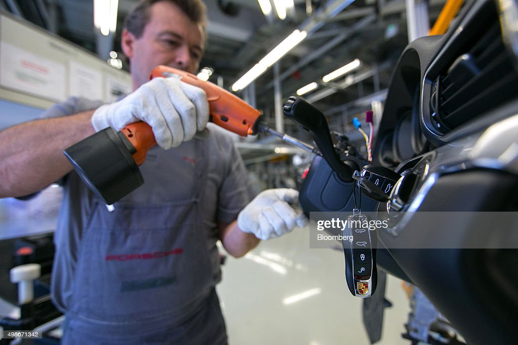 an employee secures a cover beneath the dashboard as keys sit in the