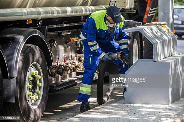 An employee secures a fuel hose from a petrol tanker as he prepares to refuel petrol pumps at a gas station operated by MOL Hungarian Oil Gas Plc in...