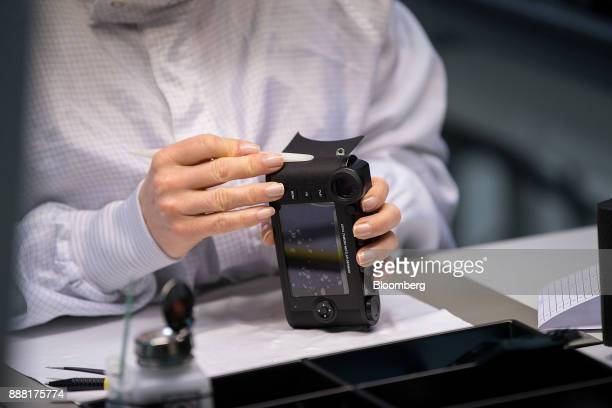 An employee secures a leather skin to the body of a Leica CL digital camera at the Leica Camera AG factory in Wetzlar Germany on Tuesday Nov 28 2017...