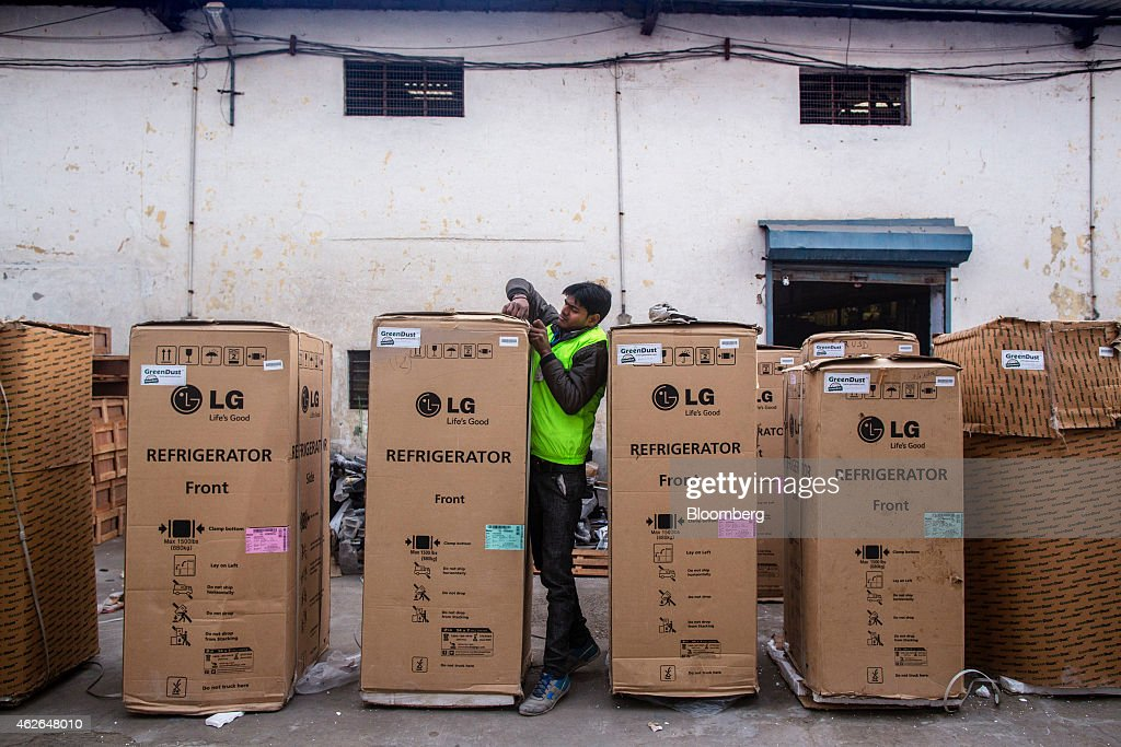 An employee secures the packaging of an LG Electronics Inc. refrigerator outside the warehouse at the refurbishment facility of GreenDust, a unit of Reverse Logistics Co., in New Delhi, India, on Friday, Jan. 16, 2015. Reverse Logistics, an Indian retailer of refurbished goods, is a factory outlet store in India selling goods through its GreenDust brand franchise stores and website. Photographer: Prashanth Vishwanathan/Bloomberg via Getty Images