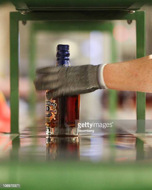 An employee selects a bottle of Chivas Regal whisky from a conveyor belt at the Pernod Ricard SA bottling plant in Paisley UK on Thursday Nov 18 2010...