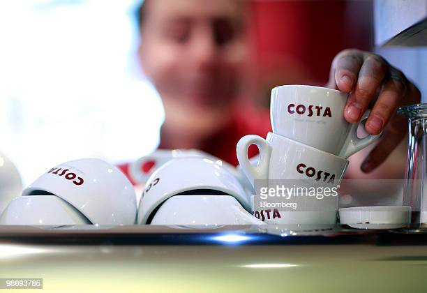 An employee selects a cup in a Costa Coffee shop in London UK on Monday April 26 2010 Whitbread Plc which own Costa Coffee announce earnings on...
