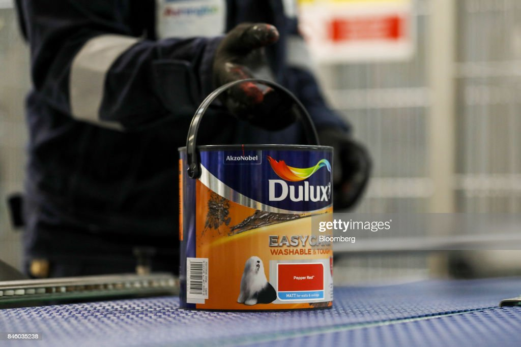 An employee selects a pot of Dulux paint from the production