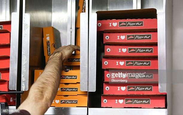 An employee selects an orange takeaway box from storage as he prepares a customer's order in the kitchen of a Pizza Hut restaurant owned by Yum...