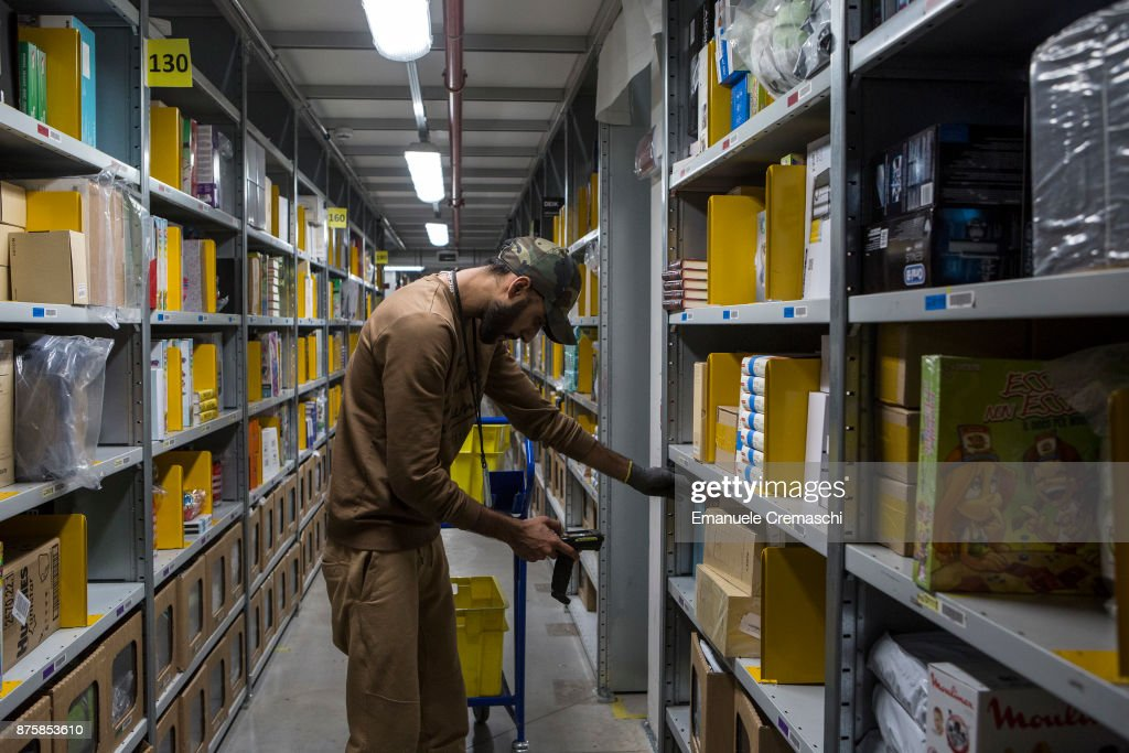 An employee selects goods from bays of merchandise as he processes customer orders at the Amazon.com MPX5 fulfillment center on November 17, 2017 in Castel San Giovanni, Italy. Established in 2014, the 100.000 sq. metres warehouse employs a workforce of 1.600 people who processed 1.2 million items during the last Black Friday.