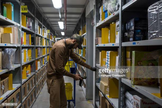 An employee selects goods from bays of merchandise as he processes customer orders at the Amazoncom MPX5 fulfillment center on November 17 2017 in...