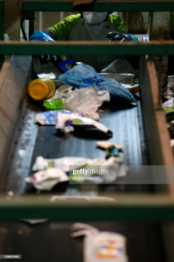 An employee separate garbage on a conveyor belt for recycling at a waste treatment plant in Burgos on January 18, 2013.