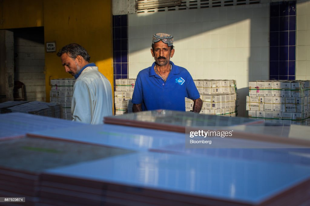 An employee separates damaged tiles before packing into boxes at the Shabbir Tiles & Ceramics Ltd. production facility in Karachi, Pakistan, on Wednesday, Dec. 6, 2017. Shabbir, which had suffered four years of losses while fighting to compete with cheap imports from neighboring China, is on course to post an annual profit next financial year after Pakistan placed an anti-dumping duty on Chinese tiles in October. That follows similar moves from the regulator on steel products. Photographer: Asim Hafeez/Bloomberg via Getty Images