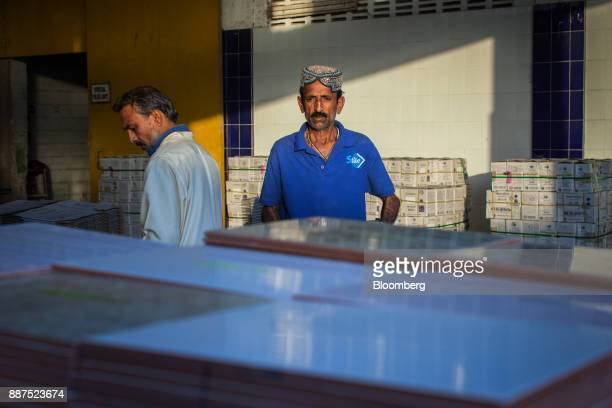 An employee separates damaged tiles before packing into boxes at the Shabbir Tiles Ceramics Ltd production facility in Karachi Pakistan on Wednesday...
