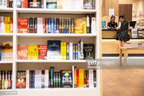 An employee serves a customer at a checkout counter in the Kinokuniya Co book store at the Aeon Mall in Phnom Penh Cambodia Sunday May 26 2019...