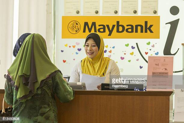 An employee serves a customer at the information counter inside a combined Malayan Banking Bhd and Maybank Islamic Bhd bank branch in Kuala Lumpur...