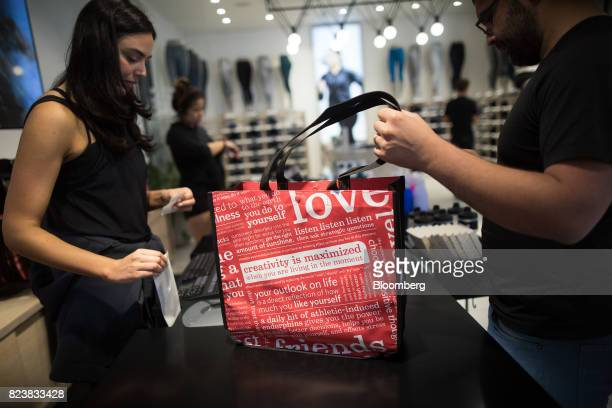 An employee serves a customer at the Lululemon Athletica Inc. Sports apparel store on Regent Street in London, U.K., on Thursday, July 27, 2017....
