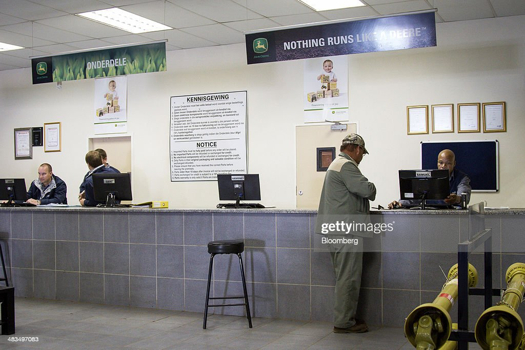 An Employee Serves A Customer At The Service Desk In The