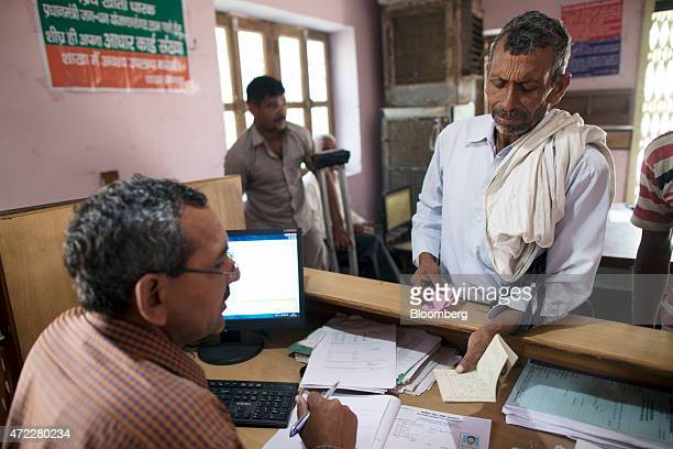 An employee serves a customer inside a branch of Gramin Bank of Aryavat sponsored by Bank of India in the village of Khurana Uttar Pradesh India on...