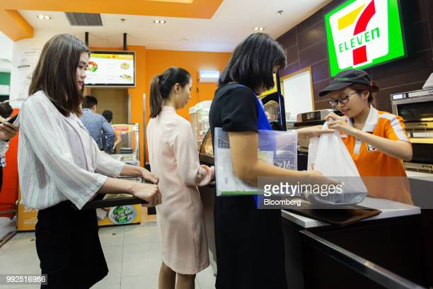An employee serves a customers at the checkout counter of a 7Eleven store in Ho Chi Minh City Vietnam on Wednesday June 20 2018 For decades...