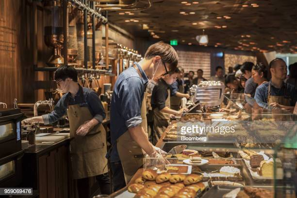 An employee serves a slice of cake at the pastry counter inside the Starbucks Corp Reserve Roastery store in Shanghai China on Friday May 11 2018...