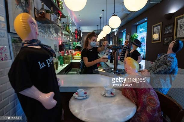 """An employee serves beer as inflatable dolls sit at the bar of """"La Pepita"""" restaurant to help clients respect social distancing rules as part of..."""