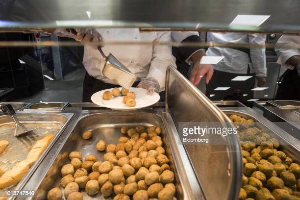 An employee serves chicken meatballs at the restaurant inside the Ikea store in Hitech City on the outskirts of Hyderabad India on Thursday Aug 9...