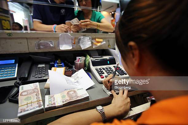 An employee serves customers as bundles of Thai onethousand baht banknotes sit on a bench at a Super Rich 1965 Co currency exchange store in Bangkok...