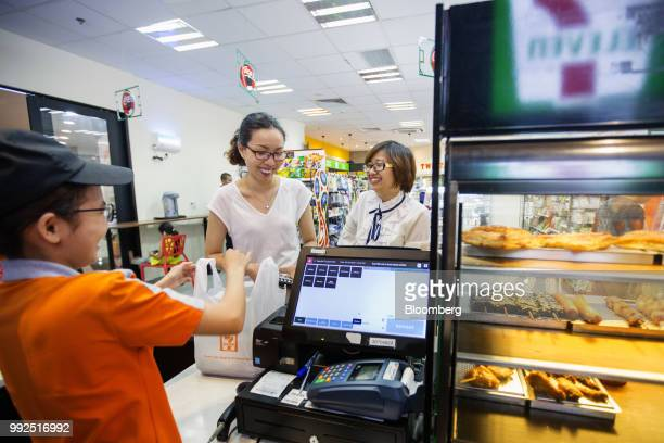 An employee serves customers at a check out counter of a 7Eleven store in Ho Chi Minh City Vietnam on Wednesday June 20 2018 For decades Vietnamese...