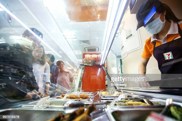 An employee serves customers at the buffet food counter of a 7Eleven store in Ho Chi Minh City Vietnam on Wednesday June 20 2018 For decades...