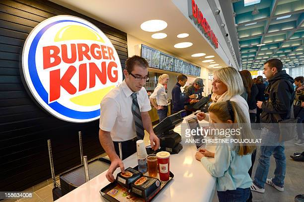 An employee serves customers at the Burger King fast food restaurant in Marseille's airport in Marignane southern France on December 22 2012...