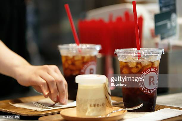 An employee serves drinks and a jar of pudding on a tray inside the Rakuten Cafe operated by Rakuten Inc in Tokyo Japan on Thursday May 29 2014...
