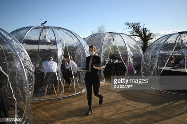 An employee serves guests in domes on the terrace outside the Black Dog Restaurant and Bar in Chester, northwest England, on April 12, 2021 as...
