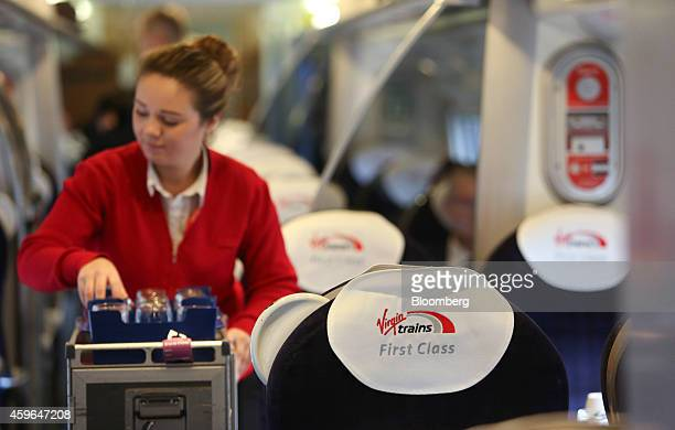 An employee serves refreshments from a snack trolley in the first class compartment of a West Coast train operated by Virgin Trains as it travels...