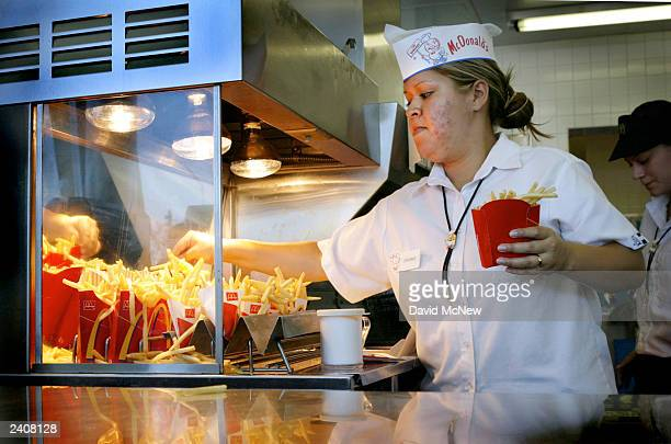 An employee serves up french fries at the world's oldestoperating McDonald's fast food restaurant on its 50year anniversary on August 18 2003 in...