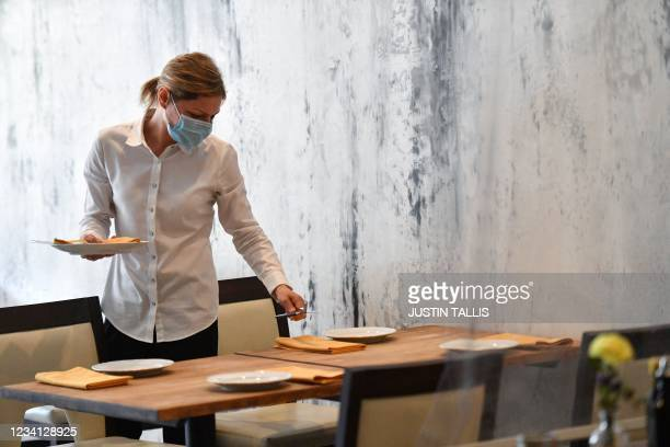 An employee sets a table at Lume restaurant and wine shop on Primrose Hill in north London on July 22, 2021. - As coronavirus cases once again soar...