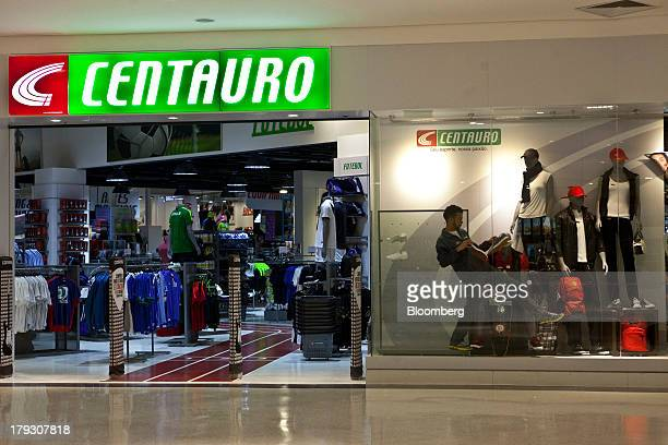 5728cd9bd6 An employee sets up a window display at Centauro sports store in the  Conviva Americas mall
