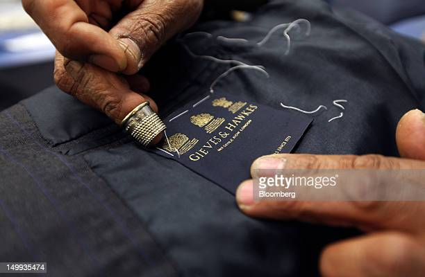 An employee sews a label into a suit jacket in the workshop at the Gieves Hawkes store owned by Trinity Ltd on Savile Row in London UK on Tuesday Aug...