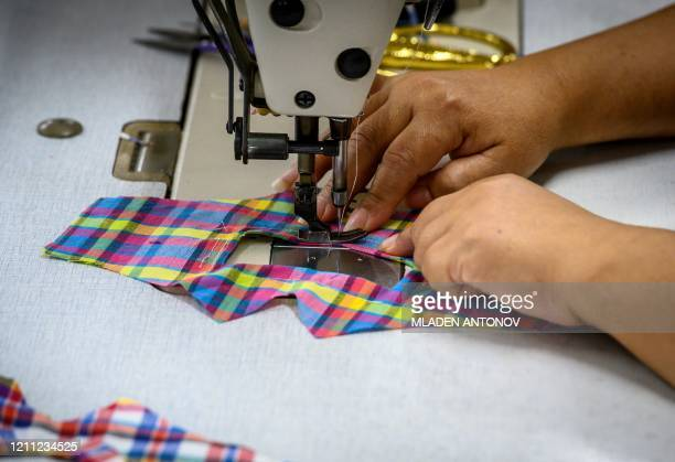 An employee sews a seethrough face mask designed for deaf people at the Center of Empowerment for the People with Disabilities in Bangkok on April 29...