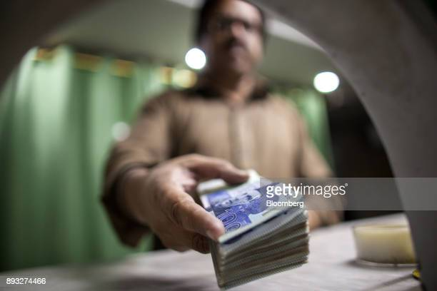 An employee shows a bundle of Pakistani one thousand rupee banknotes at a cash counter of the office of Pakistan Currency Exchange Pvt in Karachi...