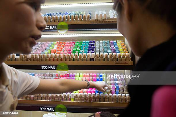 An employee shows a customer nail polish products at Amorepacific Corp's Innisfree store in the Causeway Bay district of Hong Kong China on Wednesday...