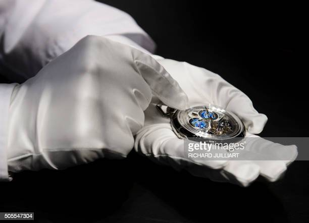 An employee shows a Montblanc watch owned by Richemont a Switzerlandbased luxury goods holding company during the opening day of the 'Salon...