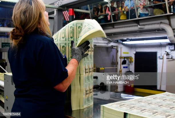 An employee shows a pack of freshly printed sheets of 20 USD notes representing a value of 200000 USD to visitors at the US Treasury's Bureau of...