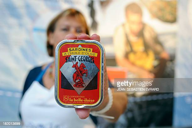 An employee shows a tin of sardines on September 25 2013 in Quiberon western France at the canning factory 'La Belle Iloise' The company employs 200...