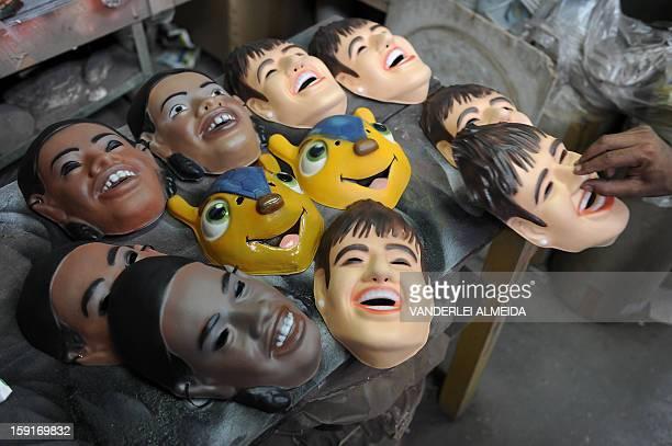 "An employee shows masks of Brazilian football stars Neymar and Ronaldinho Gaucho, and the mascot of the Brazil 2014 FIFA World Cup, ""Tatu..."