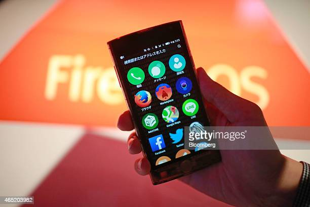 An employee shows the Firefox OS operating software on the screen of an LG Electronics Inc Fx0 smartphone in the Firefox pavilion at the Mobile World...