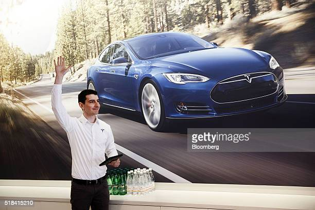 An employee signals he is ready to assist a customer with preordering the Tesla Motor Inc Model 3 ahead of the announcement outside a store on the...