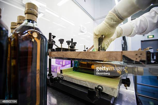 An employee silkscreen prints a gold ink design to a bottle of special edition Johnnie Walker Blue Label inside the luxury engraving finishing centre...