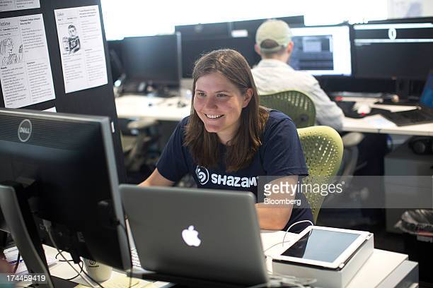 An employee sits at a desk and uses a computer at the Shazam Entertainment Ltd headquarters in London UK on Friday July 26 2013 Billionaire Carlos...