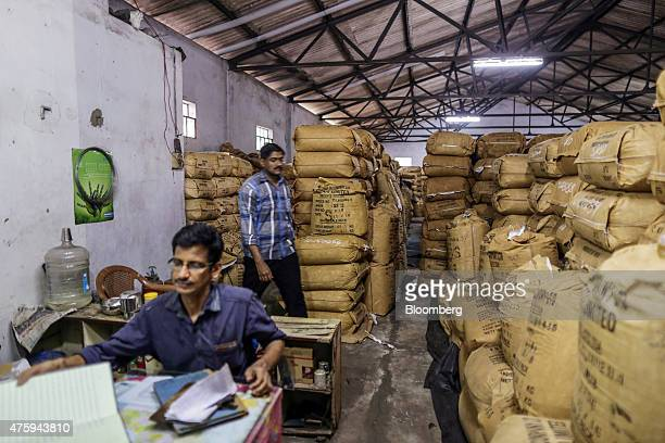 An employee sits at a desk next to bags of tea stacked in a warehouse near Cochin Port in Cochin India on Friday May 29 2015 India is gearing up for...