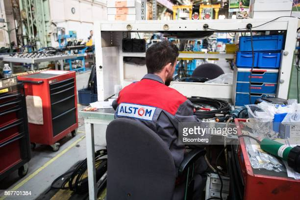 An employee sits at a workbench on the assembly line inside the Alstom SA high-speed railway train factory in Belfort, France, on Thursday, Oct. 26,...