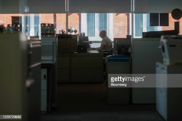 An employee sits at a workstation at offices in London, U.K., on Wednesday, June 24, 2020. Companies are getting ready to welcome more staff back to...